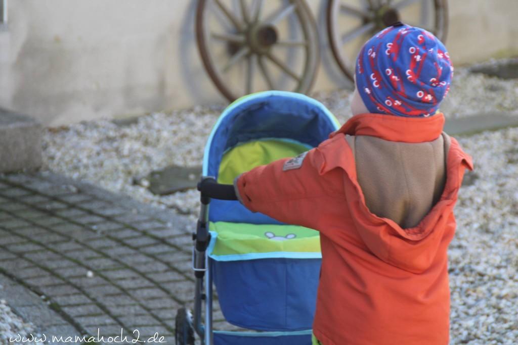 junge mit puppenwagen